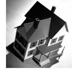 A black and white photo of a house wrecked by mortgage debt.